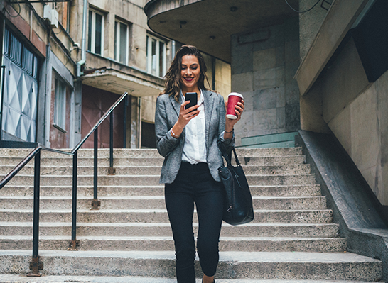 image of young lady walking down steps, using her mobile phone